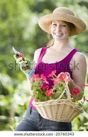 Smiling young woman cutting flowers in her garden - stock photo