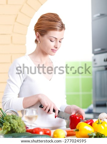 Smiling young woman cutting vegetables in kitchen.