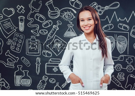 Smiling young woman doctor standing on dark background with pattern. Hands in pocket