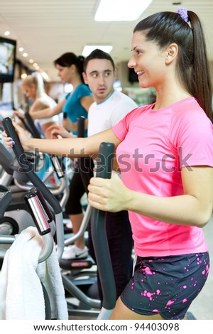 smiling young woman doing cardio workout in gym - stock photo