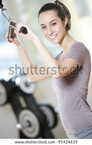 smiling young woman doing on a weight machine at the health club.