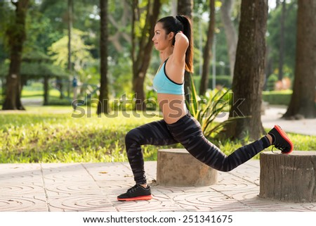Smiling young woman doing squats in the park - stock photo
