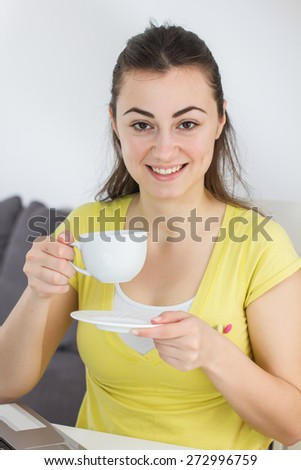 Smiling Young Woman Drinking Coffee. Caucasian brunete female at home. - stock photo