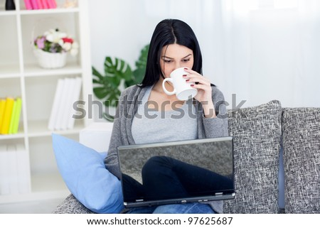 Smiling young woman drinking coffee or tea while using laptop at home