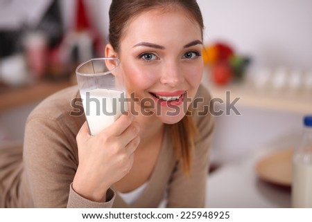 Smiling young woman drinking milk, standing in the kitchen - stock photo