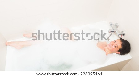 Smiling young woman enjoying in foam at bathtub