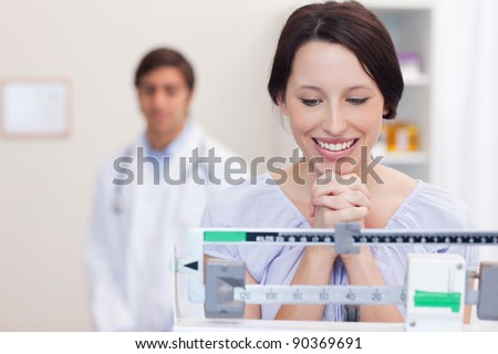 Smiling young woman excited about the scale - stock photo