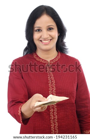 Smiling young woman giving Indian rupee notes against white background - stock photo