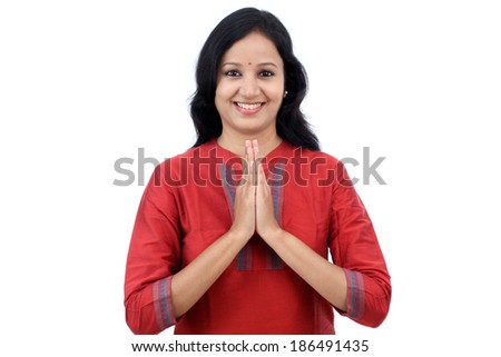 "Smiling young woman greeting ""Namasthe"" against white background - stock photo"