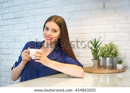 Smiling young woman having a cup of coffee at home. - stock photo
