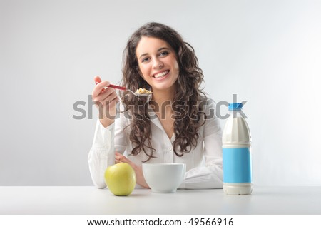 Smiling young woman having breakfast - stock photo