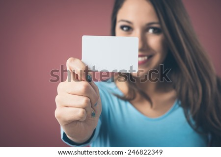 Smiling young woman holding a blank business card and looking at camera - stock photo