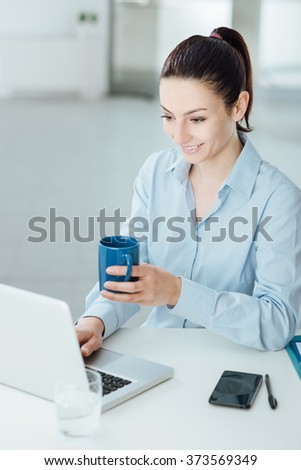 Smiling young woman holding a cup of coffee and having a break sitting at office desk - stock photo
