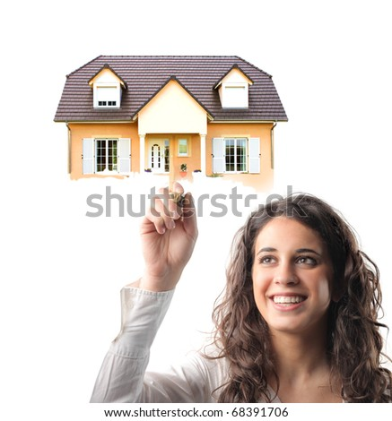Smiling young woman holding a house on her finger - stock photo