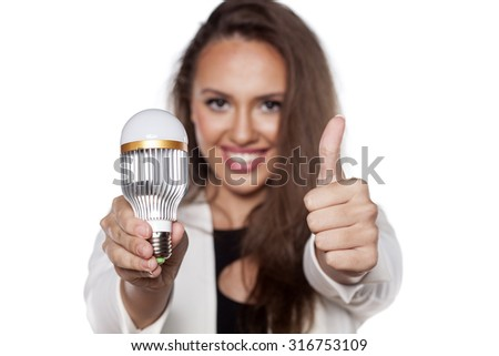 smiling young woman holding a light bulb and shows thumbs up - stock photo