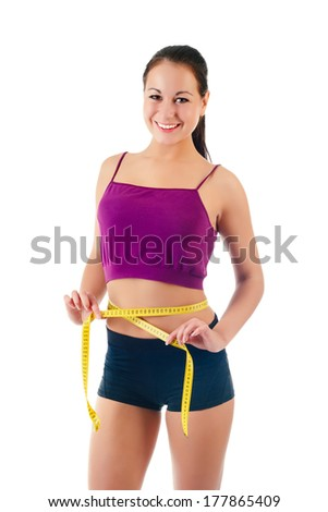 smiling young woman holding a measure tape around her waist isolated on a white background
