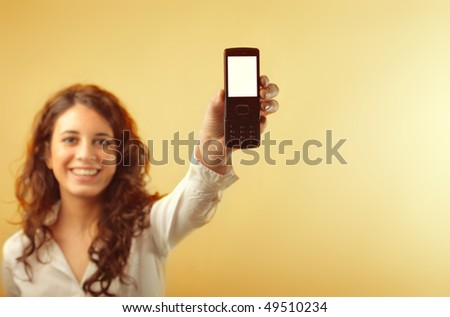 Smiling young woman holding a mobile phone - stock photo