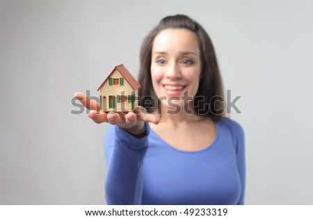 Smiling young woman holding a model of a house in her hand