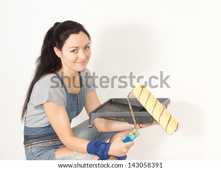 Smiling young woman holding a paint tray and roller in her hands as she prepares to start painting her house - stock photo