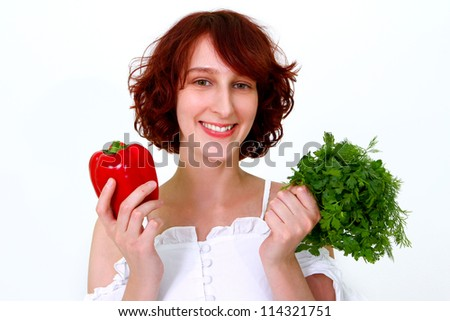 Smiling young woman holding a pepper, dill, parsley - stock photo