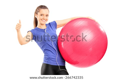 Smiling young woman holding a red exercise ball and giving a thumb up isolated on white background - stock photo