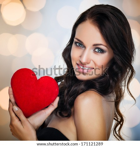 Smiling young woman holding a red heart on sparkling background - stock photo