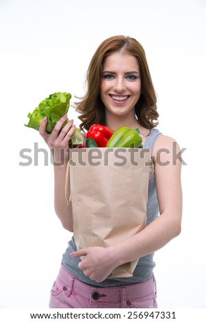 Smiling young woman holding a shopping bag full of groceries - stock photo