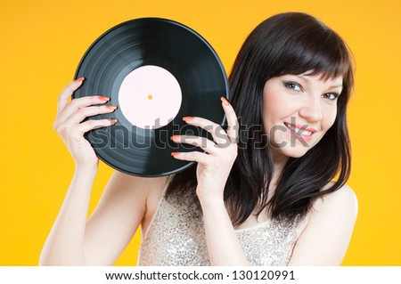 Smiling young woman holding a vinyl record and looking at camera - stock photo
