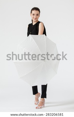 Smiling young woman holding a white umbrella, white background - stock photo