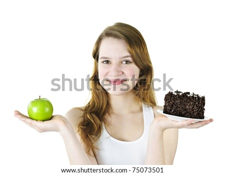Smiling young woman holding apple and chocolate cake - stock photo