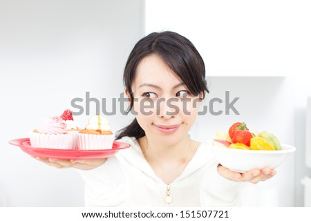 Smiling young woman holding cupcake and fruits - stock photo