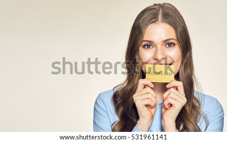 Smiling young woman holding gold credit card. isolated portrait.