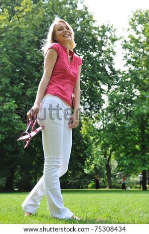Smiling young woman holding her shoes and walking barefoot on grass in park - stock photo