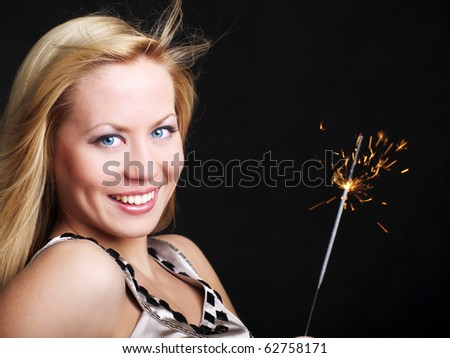 smiling young woman holding new year's sparkler over dark background
