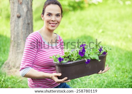 Smiling young woman holding potted plant while working in the garden - stock photo