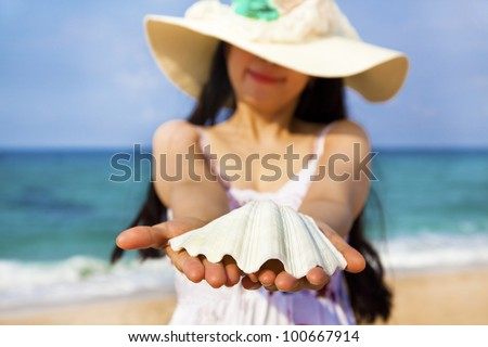 smiling young woman holding shell on the beach