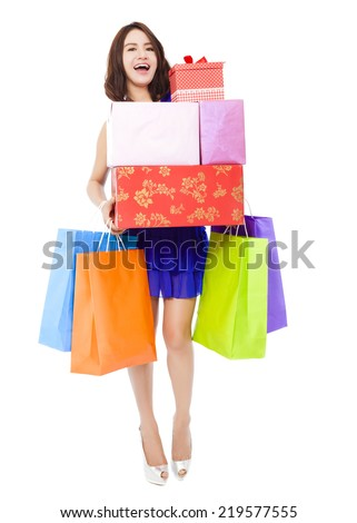 smiling young woman holding shopping bag and a gift box over white background