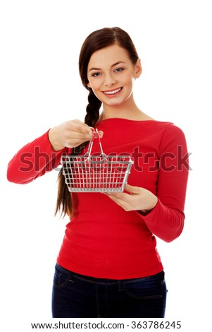 Smiling young woman holding small empty shopping cart - stock photo