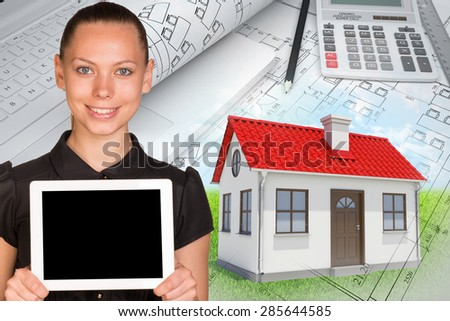 Smiling young woman holding tablet and looking at camera on abstract background with house and calculator - stock photo