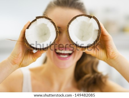 Smiling young woman holding two pieces of coconut in front of eyes - stock photo