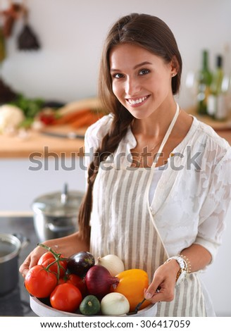 Smiling young woman holding vegetables standing in kitchen .