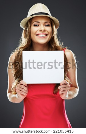 smiling young woman holding white blank board . positive emotion portrait of female model on gray studio background. - stock photo
