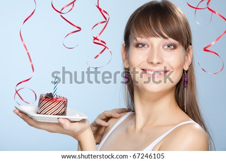 Smiling young woman holds cake with candle in her hand and confetti with ribbons on background
