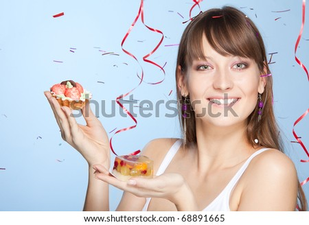 Smiling young woman holds cake with confetti and ribbons on background