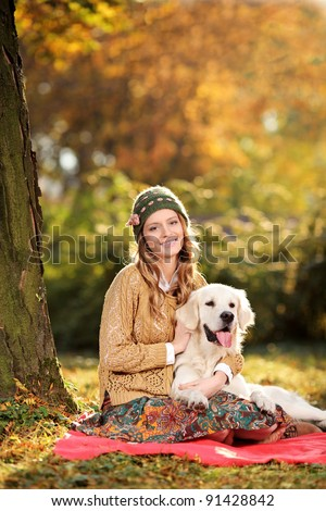 Smiling young woman hugging a labrador retriever dog out in the park - stock photo