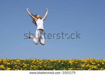 Smiling young woman in a happy jump in flowering spring field. - stock photo