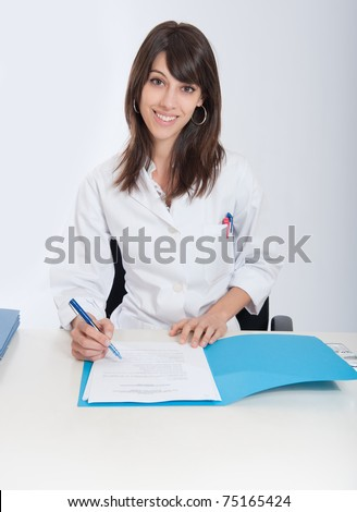 Smiling young woman in a lab coat sitting at the desk  with an open folder - stock photo