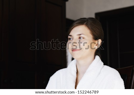 Smiling young woman in bathrobe looking sideways while sitting on chair