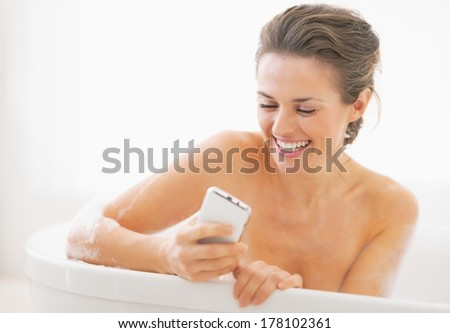 Smiling young woman in bathtub writing sms