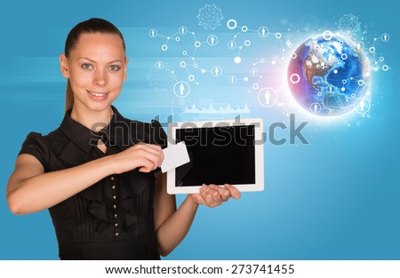 Smiling young woman in black dress holging tablet and blank card with 3d Earth model and looking at camera on abstract blue background. Elements of this image furnished by NASA
